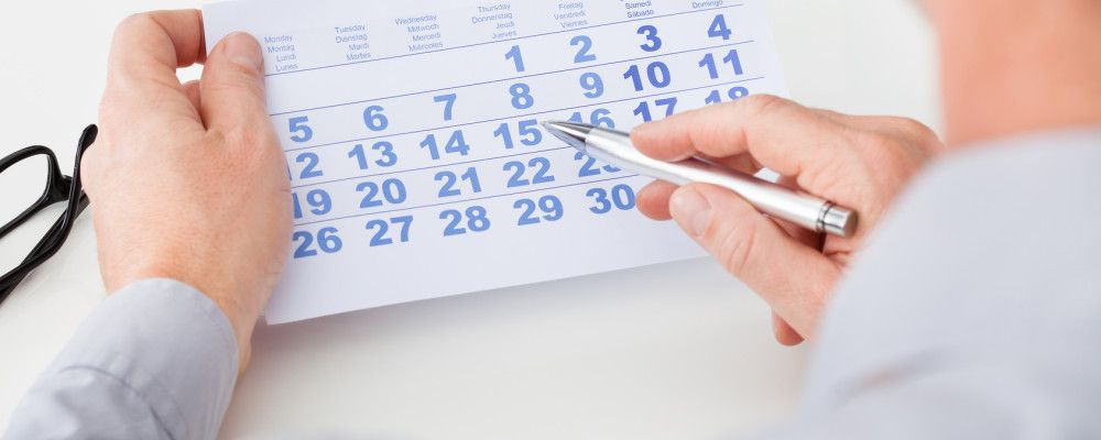 Close-up Of Man Marking With Pen And Looking At Date On Calendar